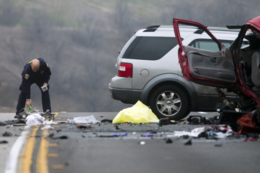 Officials investigate the scene of a multiple vehicle accident where 6 people were killed on the westbound Pomona Freeway in Diamond Bar, Calif. on Sunday morning, Feb. 9, 2013. Authorities say a wrong-way driver caused the pre-dawn crash that left six people dead.  (AP Photo/San Gabriel Valley Tri