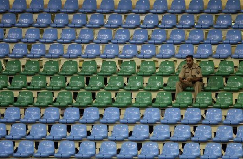 An Indian security officer sits among empty seats during the Commonwealth Games at the Indira Gandhi Sports Complex in New Delhi, India, Tuesday, Oct 5, 2010. The empty stadiums that marred the first day of competition at the crisis-hit Commonwealth Games may be filled by children and the underprivileged if attendance doesn't improve. (AP Photo/ Lee Jin-man)