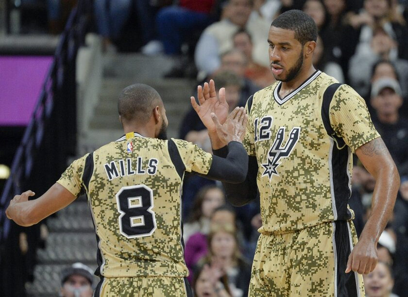 San Antonio Spurs forward LaMarcus Aldridge (12) celebrates a basket with Spurs guard Patty Mills, of Australia, during the first half of an NBA basketball game against the Charlotte Hornets, Saturday, Nov. 7, 2015, in San Antonio. (AP Photo/Darren Abate)