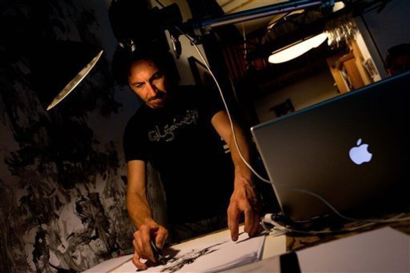In this July 20, 2011 photo, renowned visual artist Kevork Mourad practices his drawing technique before a performance in his Bushwick studio in the Brooklyn borough of New York. Bushwick's sordid history as a gang territory is becoming overshadowed by the influx of artists flocking to the area in