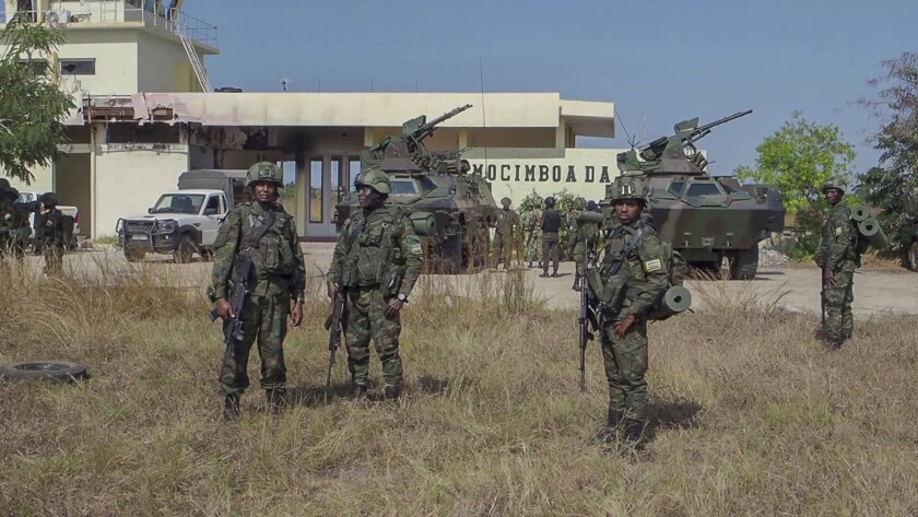 In this image made from video, Rwandan soldiers gather at the airport in Mocimboa da Praia, Cabo Delgado province, Mozambique, Monday, Aug. 9, 2021. Fresh from recapturing the strategic northern Mozambican port of Mocimboa da Praia held by Islamic extremist rebels for a year, Rwandan and Mozambican troops say they are pursuing the insurgents into the surrounding areas. (AP Photo/Marc Hoogsteyns)