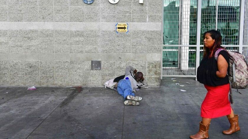 A homeless person rests near the Midnight Mission on skid row in downtown Los Angeles.