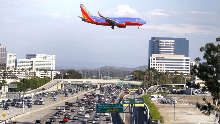 SANTA ANA CA. OCTOBER 20 2015: A plane flies over the 405 Freeway as it approaches the runway at Joh
