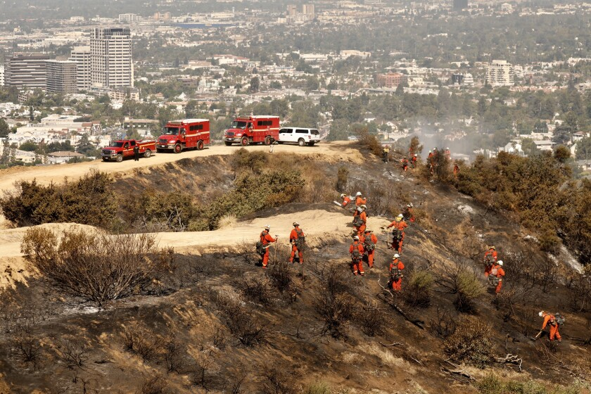 An inmate crew puts out hot spots Monday in the 45-acre brush fire in Eagle Rock.
