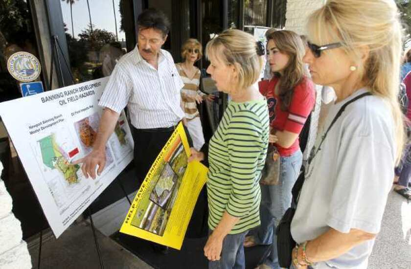 OPEN DISCUSSION - Steve Burris, far left, joins in discussion about the Banning Ranch development with Val Carson, with yellow sign, and Portia Weiss, far right, before Newport Beach City Council meeting, Monday.