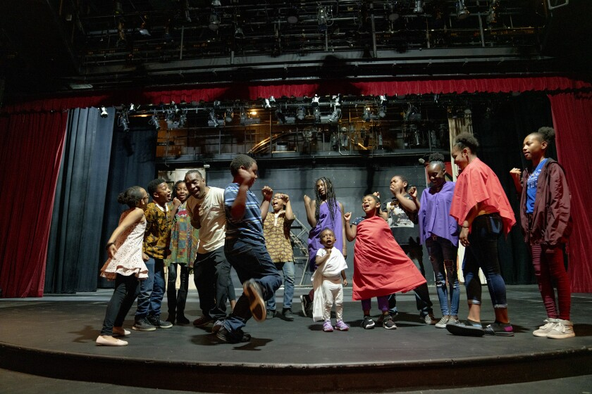 Kuumba Fest artistic director Dajahn Blevins (fourth from left) walks his cast through a scene during rehearsal at San Diego Rep.