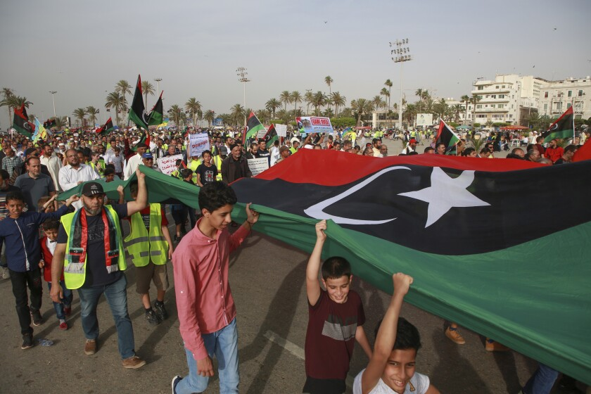 FILE - In this May 3, 2019 file photo, Libyans hold a demonstration against military operations by forces loyal to Field Marshal Khalifa Hifter, at Martyrs' Square in Tripoli, Libya. Two Libyan militia commanders and a Syrian war monitor group say Turkey is deploying Syrian extremists to fight in Libya's civil war. These extremists are affiliated with groups like al-Qaida and the Islamic State. They're fighting as mercenaries on behalf of the United Nations-supported government in Libya. (AP Photo/Hazem Ahmed, File)