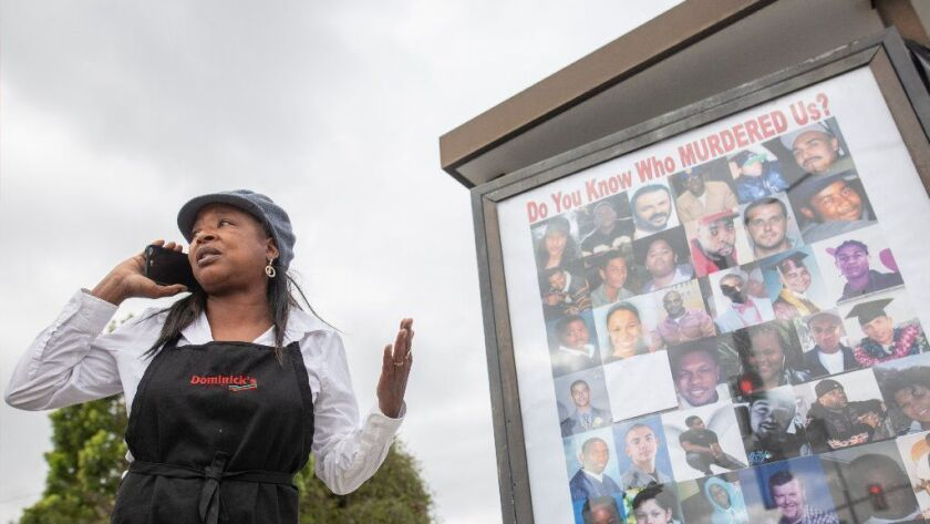 LaWanda Hawkins, whose son was killed in 1995, gives directions before unveiling the first bus shelter in a campaign featuring photographs of victims of unsolved homicides.
