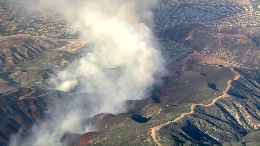 Crews battle a brush fire near Corona. The Skyline fire did not grow overnight, and 1,500 homes that were threatened no longer are, authorities said Friday.