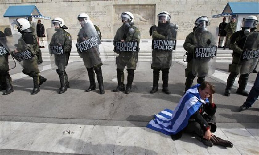 A protester wearing a Greek flag sits in front of riot police during a rally outside the Greek Parliament in Athens, Saturday, Feb. 11, 2012. The leaders of the two parties backing Greece's coalition government called on their deputies Saturday to back legislation that calls for harsh new austerity measures - essential if Greece is to get a new bailout deal worth euro 130 billion ($171.6 billion) and stave off bankruptcy. (AP Photo/Thanassis Stavrakis)