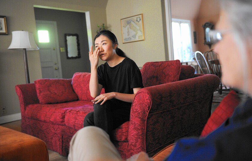Binna Kim, the lone survivor of a murder-suicide by her father a decade ago, becomes emotional while visiting with her eighth-grade English teacher, Annie Costanzo.