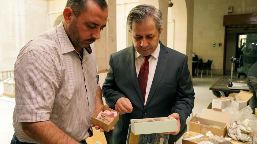 Maamoun Abdulkarim, right, Syria's director of antiquities, at the National Museum in Damascus with
