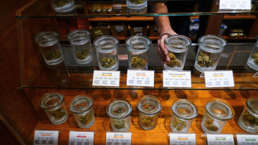 One budtender at Torrey Holistics reached into the display case for a jar containing a bud for a cus