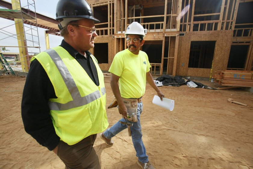 Marc Harris (left), owner of Performance Drywall & Insulation in San Diego, walks with foreman Guillermo Cardenas at a job site off Aero Drive.