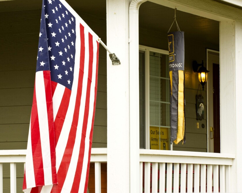 An American flag and an Army windsock fly at a home in Walla Walla, Wash.