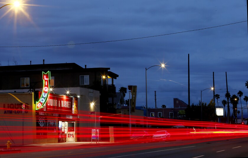 Car taillights appear as red streaks in a timed-exposure photo of Figueroa Street in South Los Angeles
