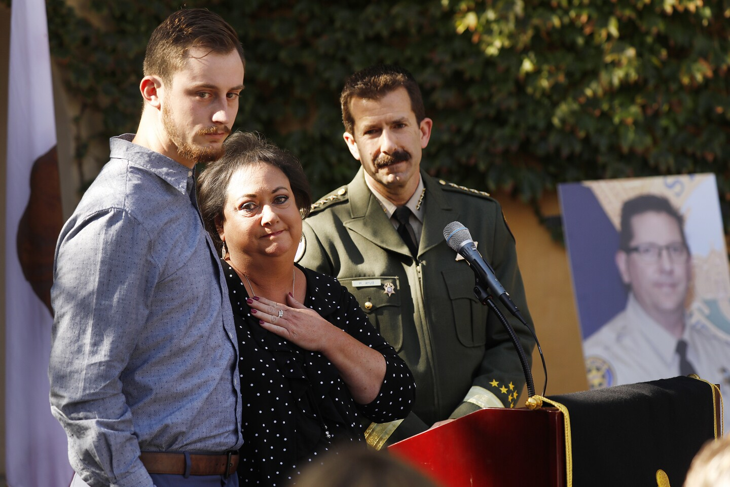 """THOUSAND OAKS, CA - NOVEMBER 6, 2019 Karen Helus, wife of Ventura County Sheriff's Sgt. Ron Helus who was killed in the line of duty during the Borderline Bar and Grill mass shooting one year ago with their son Jordan, left, and Ventura County Sheriff Bill Ayub at her side during a ceremony to dedicate a 3.4 mile section of Highway 101 between Hampshire Road and Lynn Road as the Sgt. Ron Helus Memorial Highway. """"I just wanted to say thank you to Jacqui because I know how much love went into this, I know how much hard work went into this,"""" Karen Helus said. """"And it just makes his life and his legacy keep going."""" This stretch of highway is immediately adjacent to the Borderline Bar & Grill, the location of the shooting. Assemblymember Jacqui Irwin (D – Thousand Oaks) introduced Assembly Concurrent Resolution (ACR) 17 to name the portion of U.S. Highway 101 to honor Ventura County Sergeant Ron Helus who was killed in the line of duty while responding to the active shooter threatening the lives of more than 200 college students and residents on November 7th, 2018 in Thousand Oaks. The event hosted by the Ventura County Sheriff's Office and the City of Thousand Oaks at Los Robles Greens Golf Course occurred as the signs were unveiled on the 101 freeway. """"Although this is a small gesture, I hope that by dedicating a stretch of a highway traveled by so many in the region, we can continue to be reminded of Ron's legacy of service and sacrifice to our community,"""" Assemblymember Irwin said. (Al Seib / Los Angeles Times)"""