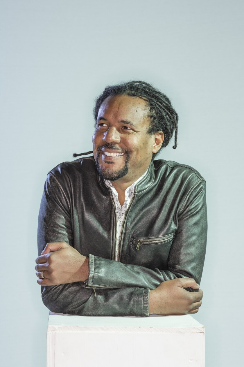 Author Colson Whitehead, wearing a dark jacket and dreadlocks, leans on a white pedestal.