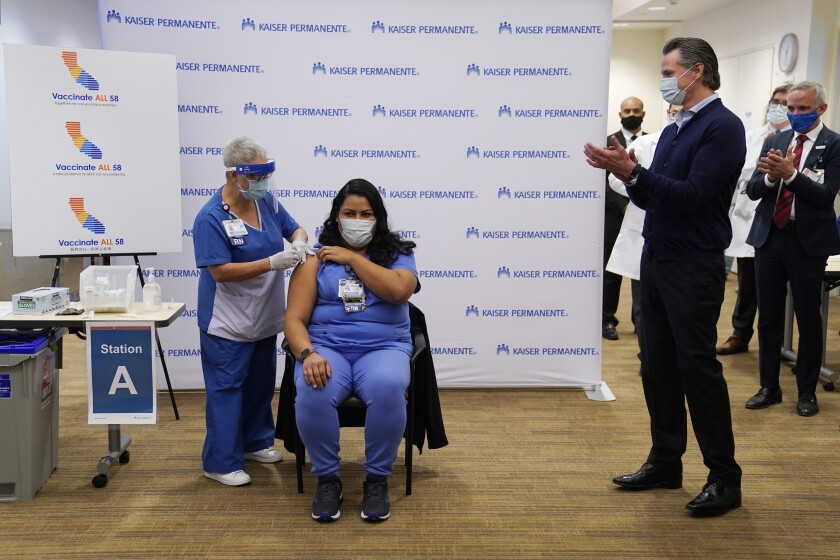 California Gov. Gavin Newsom looks on, far right, as ICU nurse Helen Cordova receives the Pfizer-BioNTech COVID-19 vaccine at Kaiser Permanente Los Angeles Medical Center in Los Angeles, Monday, Dec. 14, 2020. (AP Photo/Jae C. Hong)