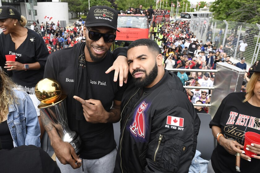 Toronto Raptors forward Kawhi Leonard points at his playoffs MVP trophy as he poses with performing