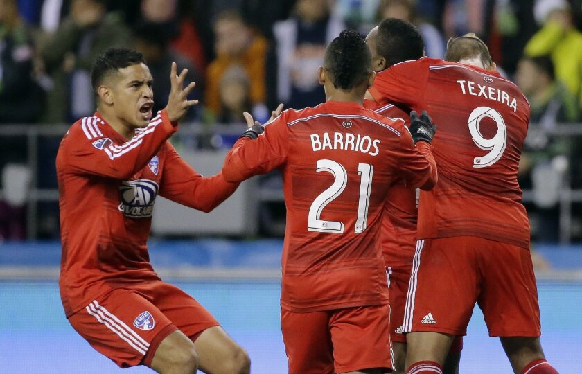FC Dallas' Mauro Diaz, left, rushes to join teammates Michael Barrios (21) and David Texeira (9) in celebrating after Dallas' Fabian Castillo scored a goal against the Seattle Sounders in the first half of an MLS soccer western conference semifinal playoff match, Sunday, Nov. 1, 2015, in Seattle. (