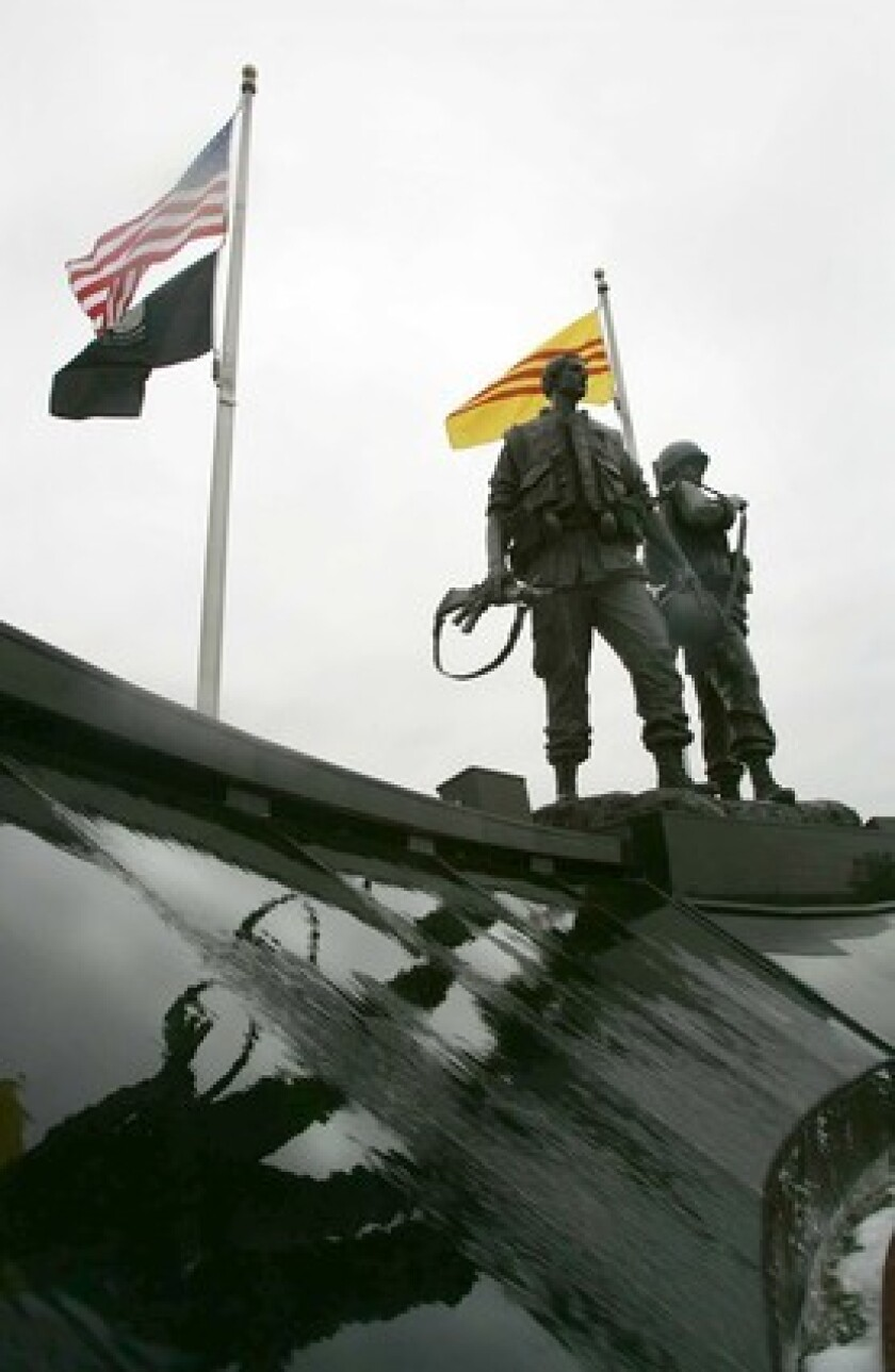 A Vietnam veteran traces a name on the Vietnam Veterans Memorial