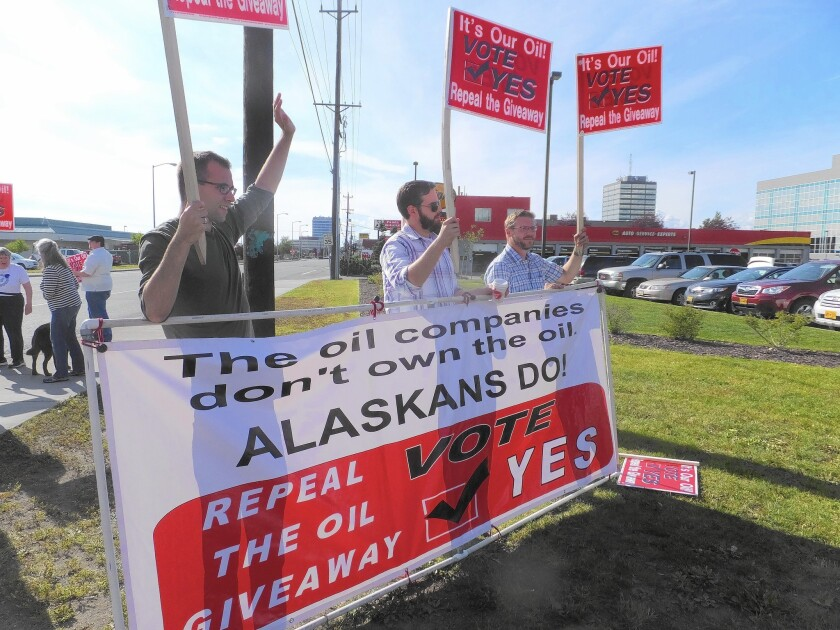 Supporters of an effort to repeal oil tax cuts approved by the Alaska Legislature in 2013 wave signs along an Anchorage street in August.
