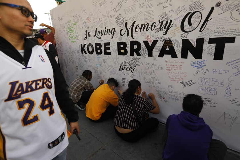Fans write personal memorials for Lakers legend Kobe Bryant at L.A. Live on Jan. 31, 2020.