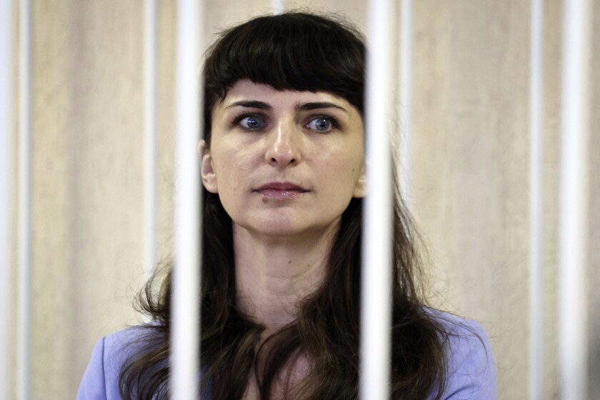 Belarusian journalist Katsiaryna Barysevich, seen in cage, attend a court hearing in Minsk, Belarus, Tuesday, March 2, 2021. On Tuesday, the Moskovsky District Court in Minsk sentenced Barysevich to six months in prison and a fine equivalent to $1,100. It also handed a two-year suspended sentence to Artsyom Sarokin, a doctor who treated protester and shared his medical records with Barysevich, and fined him the equivalent of $550. (Sergei Sheleg/BelTA Pool Photo via AP)