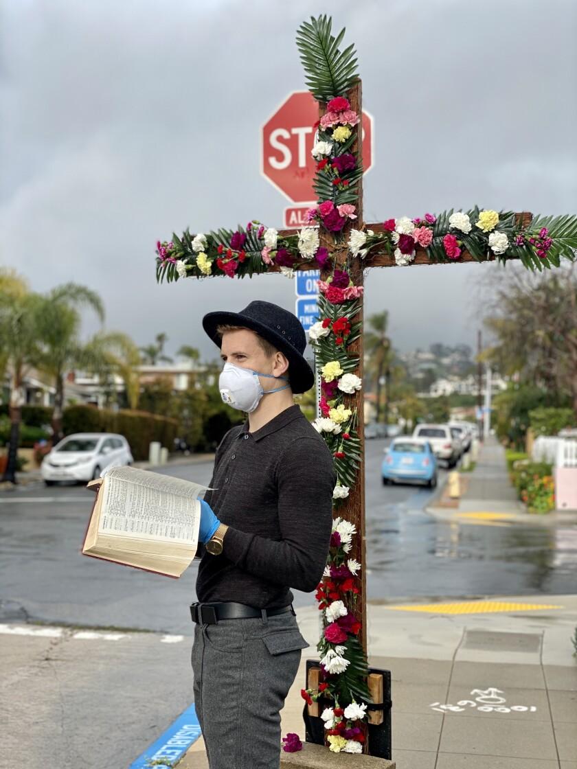 Youth pastor Harry Wilson waits to pray with congregants under the La Jolla Christian Fellowship's flower cross.