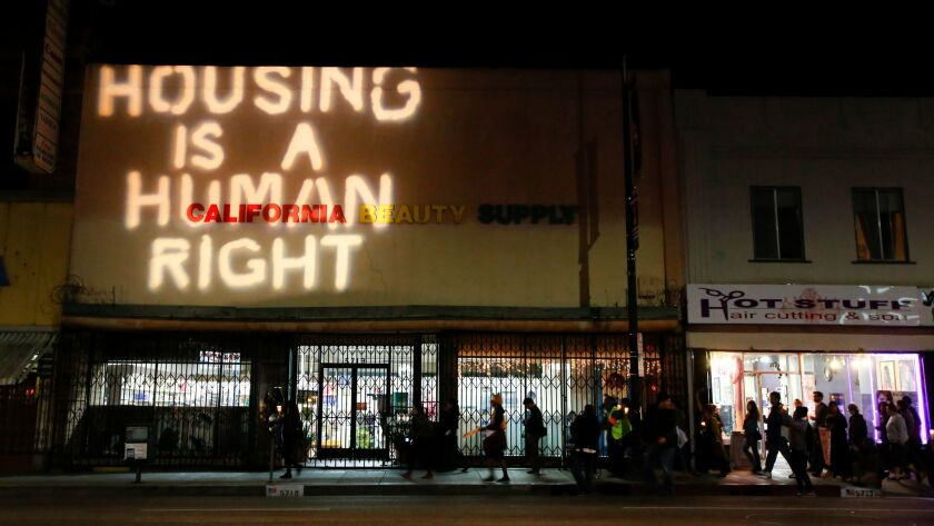 A phrase of protest is projected onto a building during a 2014 event against evictions in Highland Park. L.A. City Councilman Gil Cedillo, who is running for reelection, has been criticized by constituents who say he's not doing enough to stop displacement of renters.