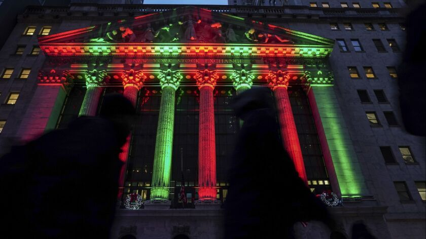 Pedestrians walk past the New York Stock Exchange, illuminated with holiday colors, on Dec. 17, 2018.