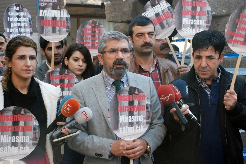 "Tahir Elci, the head of Diyarbakir Bar Association, speaks to the media shortly before being killed in Diyarbakir, Turkey, Saturday, Nov. 28, 2015. Elci, a prominent lawyer, who faced a prison term on charges of supporting Turkey's Kurdish rebels, has been killed in an attack in Diyarbakir. Elci was shot on Saturday while he was making a press statement in front of a historical mosques damaged during fightings between Kurdish rebels and security forces. Elci holds a placard that reads: "" Let's protect humanity heritage."" (IHA agency via AP) TURKEY OUT"