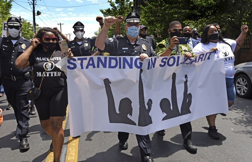 Camden County Metro Police Chief Joe Wysocki raises a fist while marching with residents and activists on May 30.