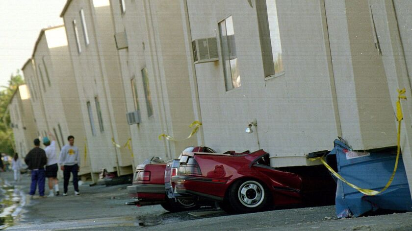 Crushed cars sit underneath a collapsed apartment building in the 19100 block of Victory Boulevard after the 1994 Northridge earthquake.