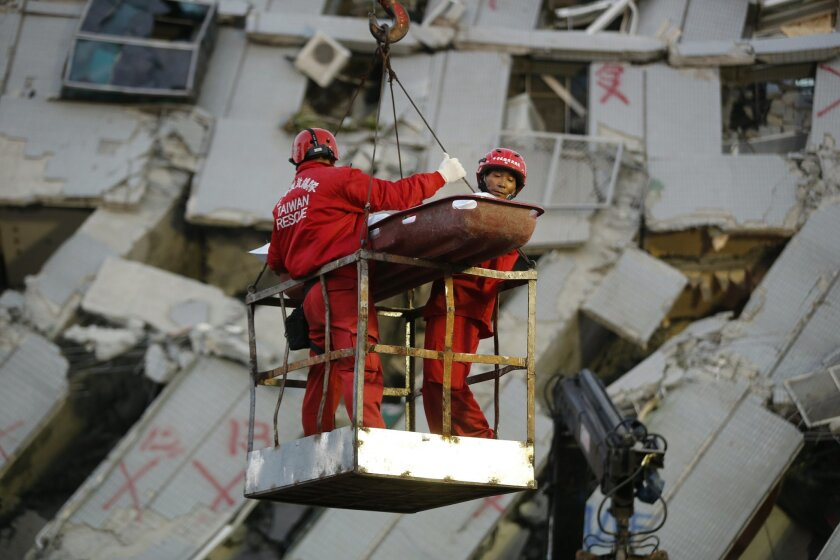Two emergency workers carry a victim recovered from a collapsed building in Tainan, Taiwan, Sunday, Feb. 7, 2016. Rescuers on Sunday found signs of live within the remains of a high-rise residential building that collapsed in a powerful, shallow earthquake in southern Taiwan that killed over a doze