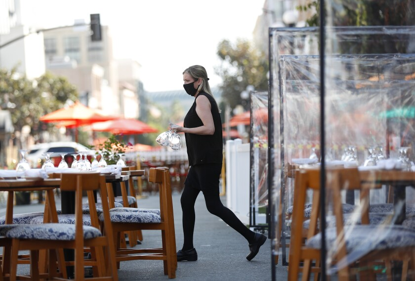An employee prepares outdoor tables at a restaurant Fifth Avenue in San Diego.