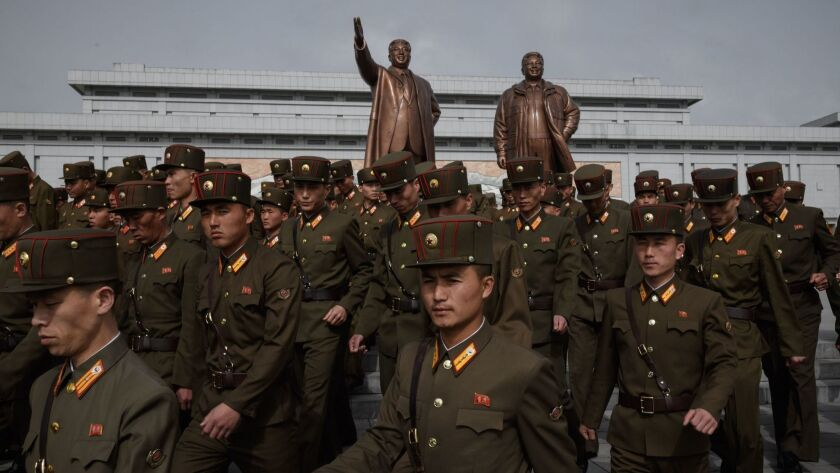 Korean People's Army soldiers pay respects before the statues of late leaders Kim Il Sung and Kim Jong Il in Pyongyang on Sunday.