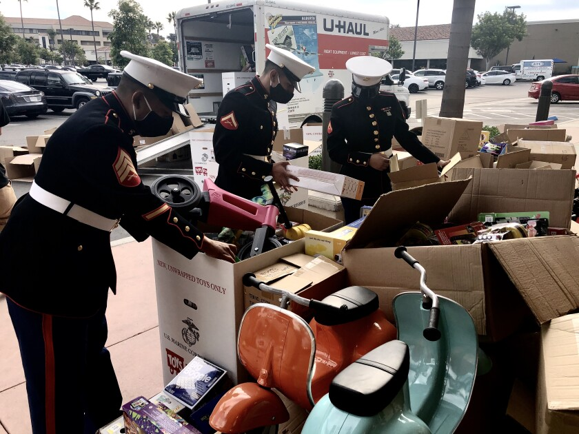 Sgt. Federico Sanchez (l) and fellow Marines sort Toys for Tots donations by an anonymous philanthropist.