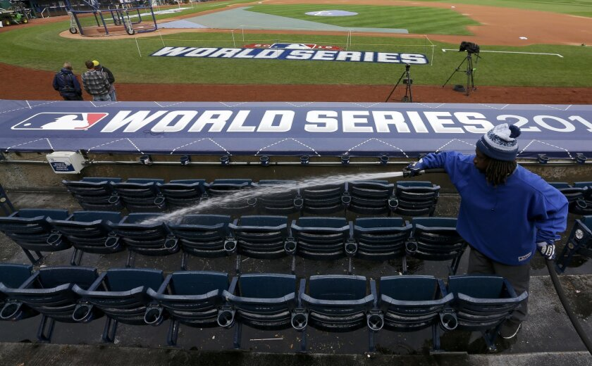 Grounds crew worker, William Williams washes down seats in preparation for the Major League Baseball World Series between the Kansas City Royals and the New York Mets.