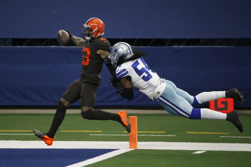 File-This Oct. 4, 2020, file photo shows Cleveland Browns wide receiver Odell Beckham Jr., (13) scoring a touchdown after a long run as Dallas Cowboys linebacker Jaylon Smith (54) attempts the stop in the second half of an NFL football game in Arlington, Texas. Beckham Jr. believes he and his teammates are poised to do something big this season. Appearing at his youth football camp, Beckham, who has made a speedy recovery from a season-ending knee injury in 2020, said there's a vibe about the Browns. (AP Photo/Michael Ainsworth, File)