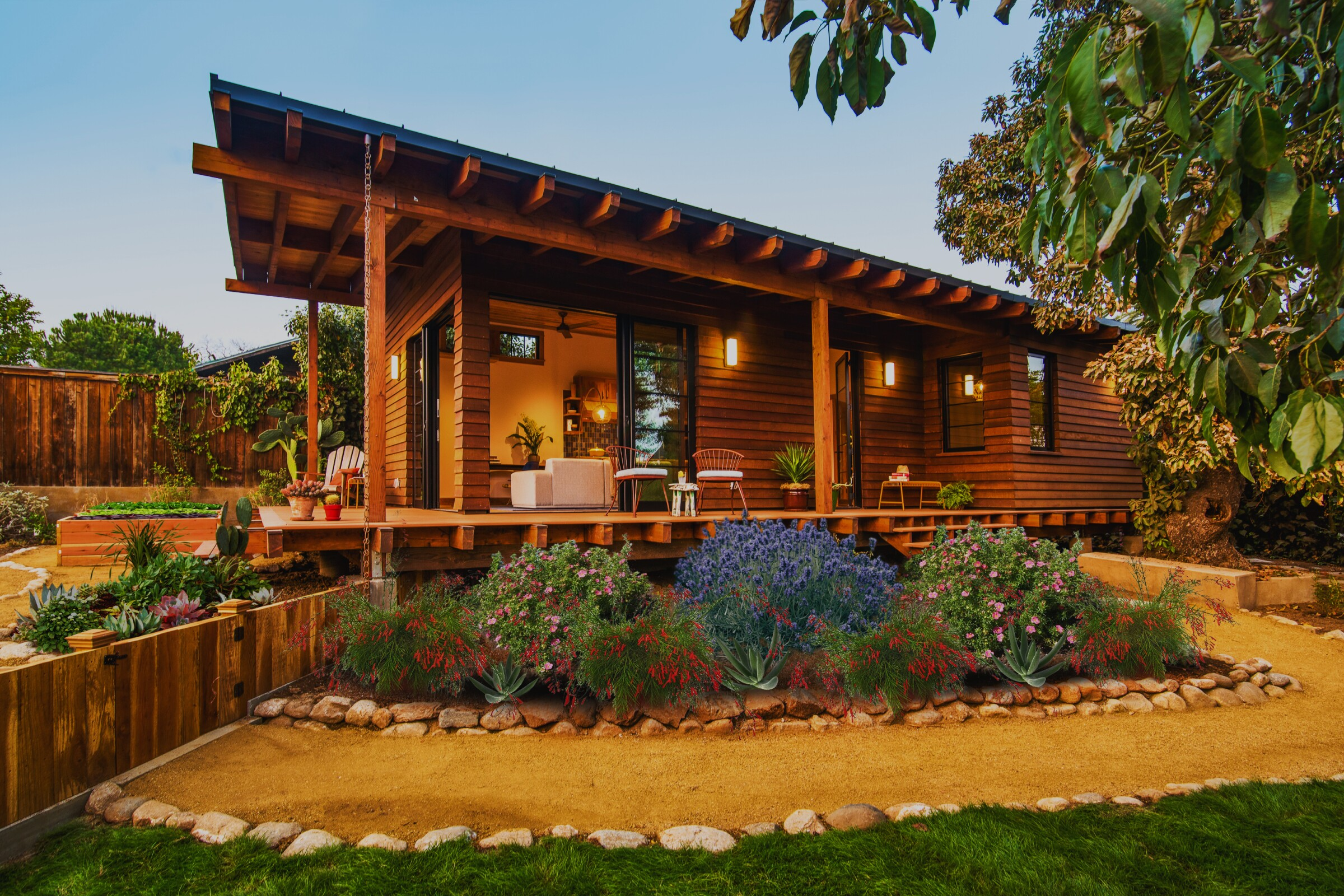 An exterior shot of a quaint 'granny flat' with redwood siding and a wraparound deck