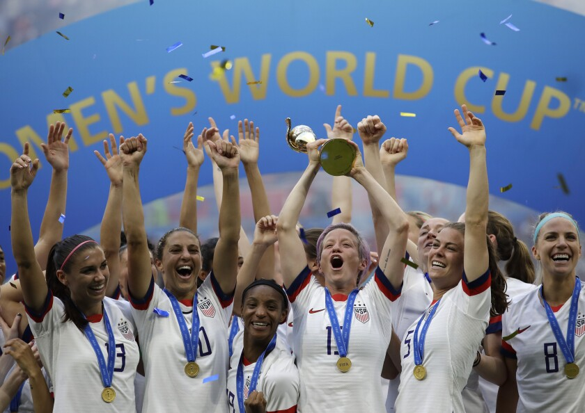 The United States' Megan Rapinoe lifts trophy and celebrates with teammates after winning
