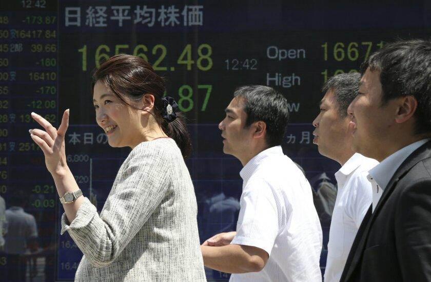 People walk by an electronic stock board of a securities firm in Tokyo, Monday, May 23, 2016. Japanese stocks fell and other Asian markets were higher Monday after a global finance meeting failed to produce an economic growth plan and Tokyo reported weaker exports. (AP Photo/Koji Sasahara)