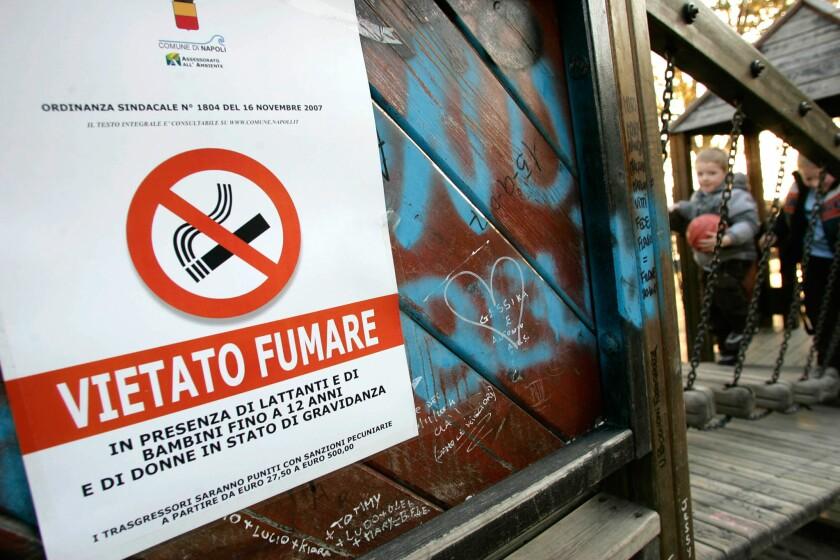 """ARCHIVO - Anuncio que prohíbe fumar """"en presencia de bebés y niños menors de 12 años y de mujeres embarazadas"""" colocado en un parque de juegos infantiles en Nápoles, en el sur de Italia, en esta fotografía de archivo."""