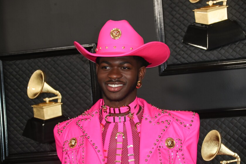 A man posing in a hot pink cowboy suit and hat