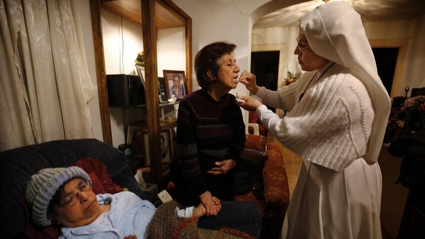 Sister Maria Socorro gives holy communion to Yolanda Calderon at the beside of her sister, Esperanza.