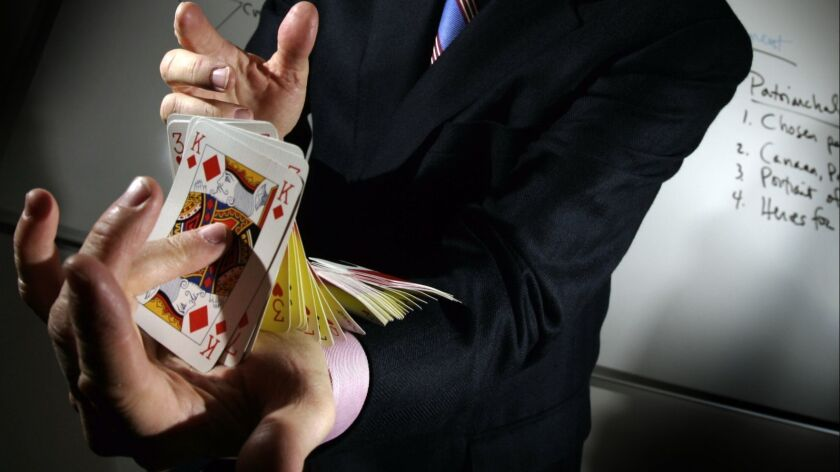 A magician performs a card trick in Glendora.