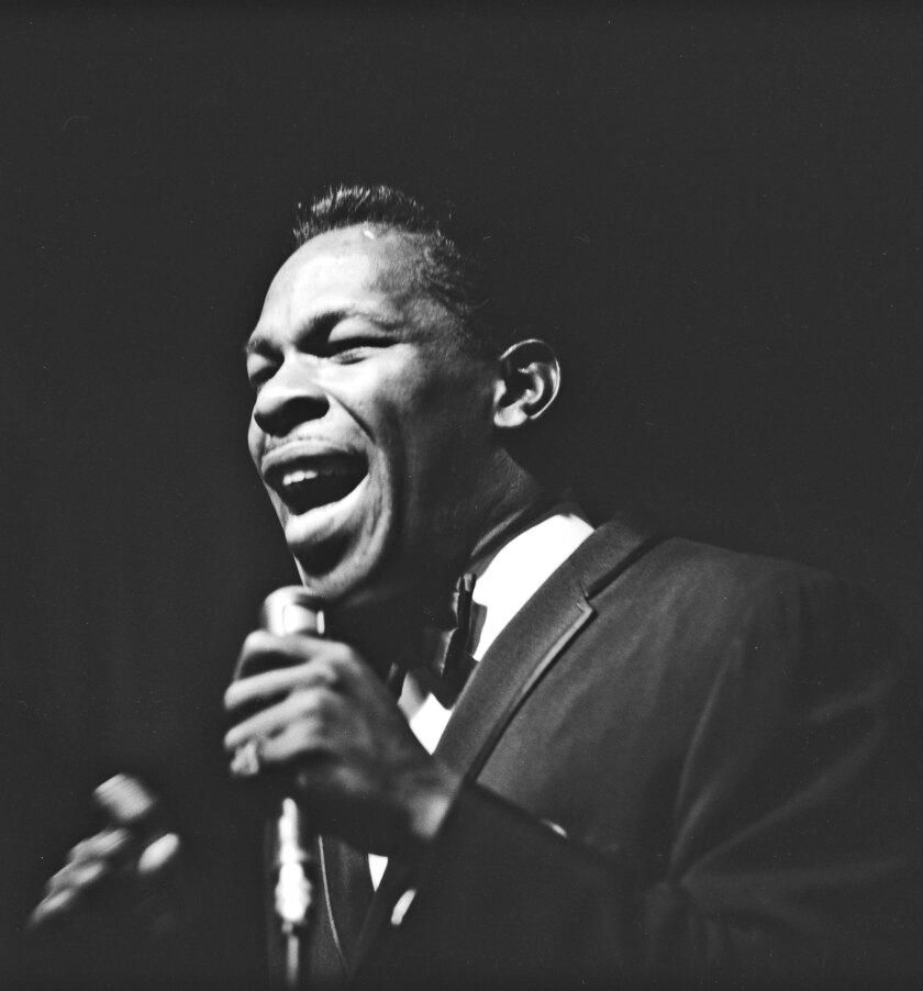 Wearing a suit and tie, Lloyd Price sings into a microphone.