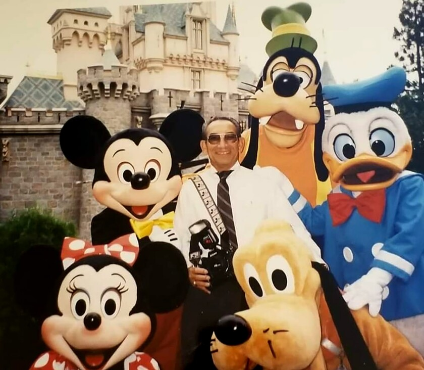 Renie Bardeau, camera strapped over a shoulder, poses with costumed characters at Disneyland.